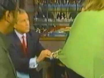 G W Bush wiping his glasses on someone's jacket
